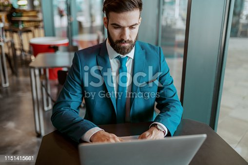 istock Young adult focused businessman in blue suit sitting at cafe and using laptop for work. 1151415661