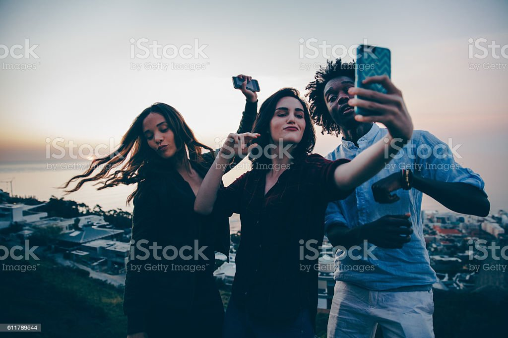 Young adult friends dancing and taking selfie with smart phone stock photo