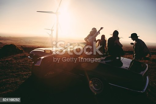 Group of young adult friends is partying at sunset with a guitar and singing leaned to their convertible parked under some large wind turbines