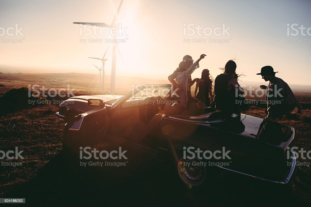 Young adult friends enjoing time together with guitar at sunset stock photo