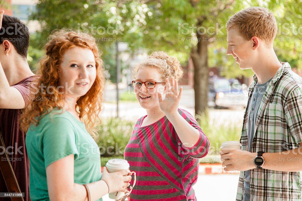 Young adult friends hanging out in urban, downtown city. stock photo