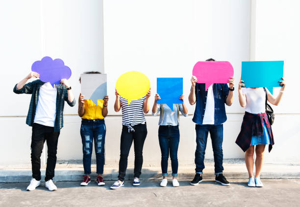 Young adult friends holding up copy space placard thought bubbles Young adult friends holding up copy space placard thought bubbles speech bubble stock pictures, royalty-free photos & images