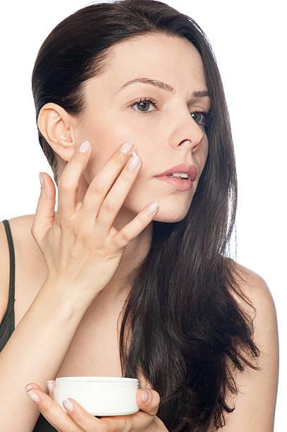 Young adult girl applying moisturiser cream stock photo