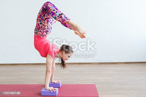 A gymnast girl performs a handstand in the training room against a white wall.