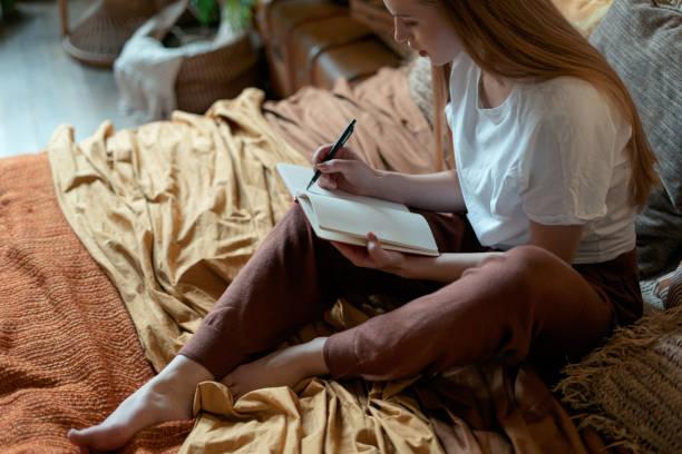 ung vuxen flicka vilar hemma på mysiga sovrum - dagbok bildbanksfoton och bilder
