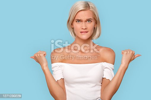 Portrait of unsure young adult girl looking at camera, biting low lip, showing aside with fingers. Woman making choice while standing isolated on pastel blue background