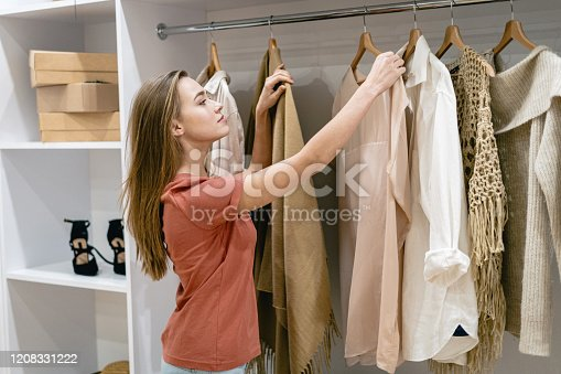 Side view of calm, young adult girl standing near wardrobe, choosing stylish clothes, compared trendy options, making thoughtful face