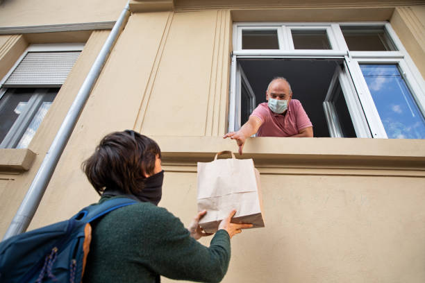 jonge volwassene die een zak met het winkelen aan zijn vader door het venster geeft - raam bezoek stockfoto's en -beelden