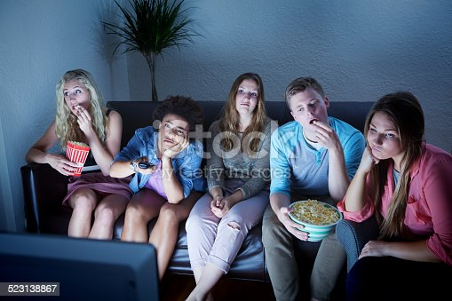 A group of young people watching TV and totally bored by the programming.