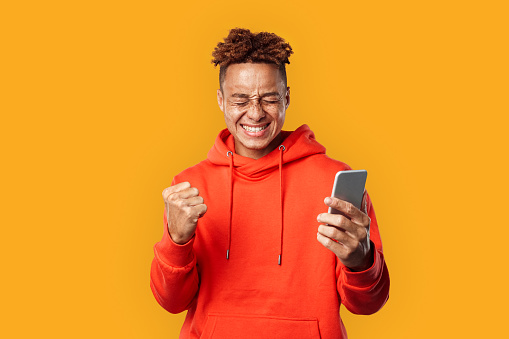 Young adult guy holding modern smartphone and rejoiced