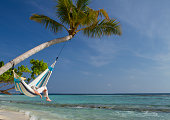 A young man is having a nap in a hammock over the sea.