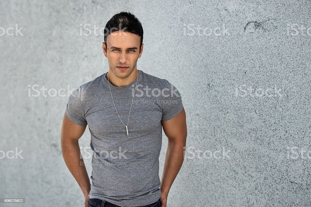 young adult handsome man wearing grey casual t-shirt posing stock photo