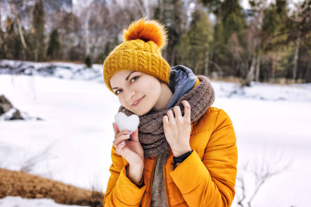 Young adult happy woman, portrait on the background of a beautiful winter mountain landscape in nature with a snow heart in her hands stock photo