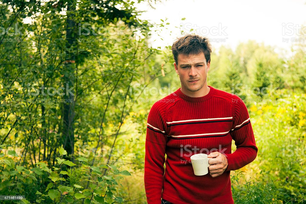 Young Adult having a coffee in the forest royalty-free stock photo