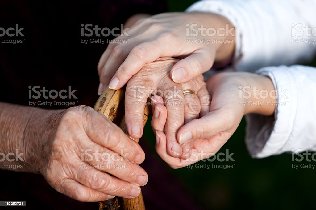 Young adult helping senior women, holding hands royalty-free stock photo