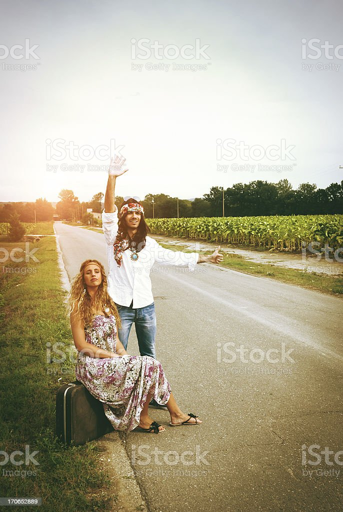 Young adult hippie couple hitchhiking royalty-free stock photo