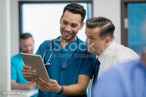istock Young adult Hispanic nurse consults with senior doctor using digital patient chart 1075790178