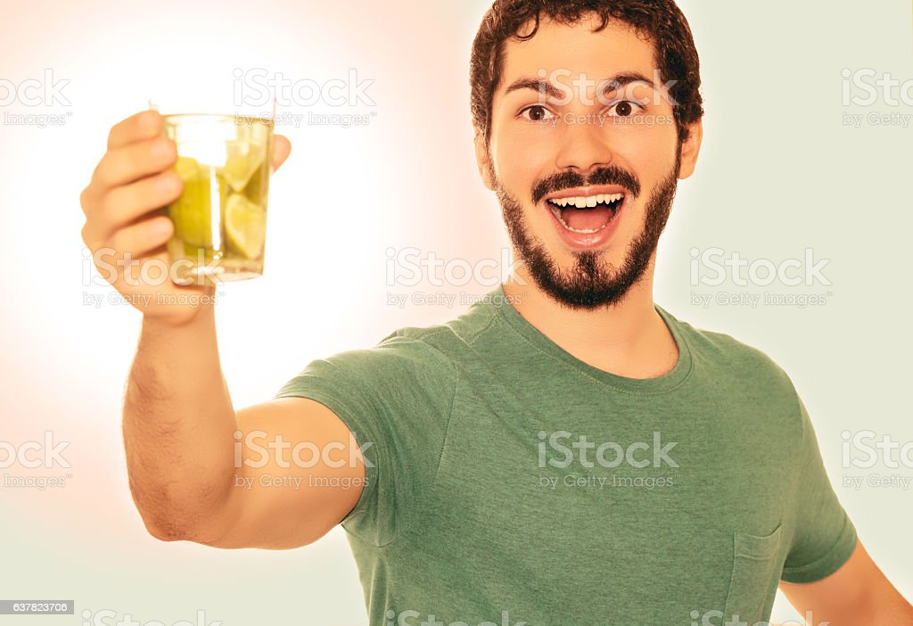 Young adult holding a glass of drink made of lemon. stock photo