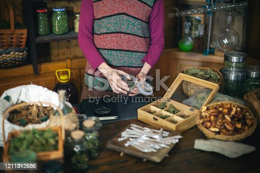 Young Adult Holding Batch of Dry Cannabis in Rustic Herbal Shop - Stock Photo