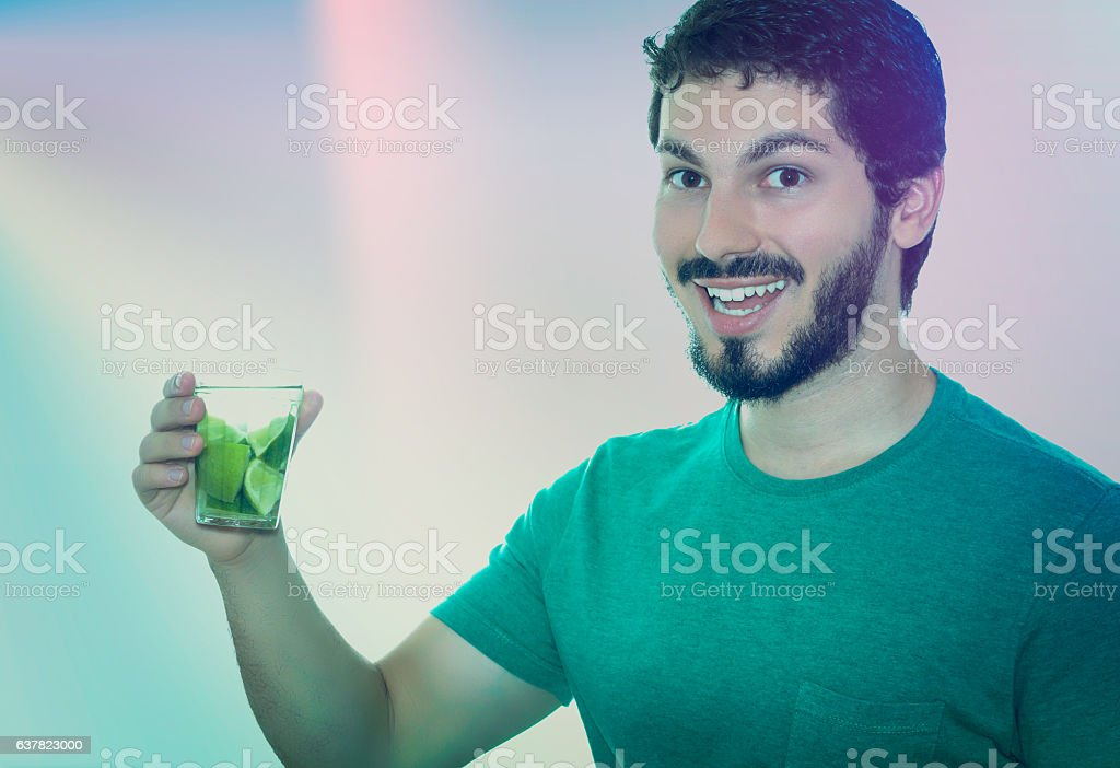 Young adult holding cup of caipirinha, looking at the camera stock photo