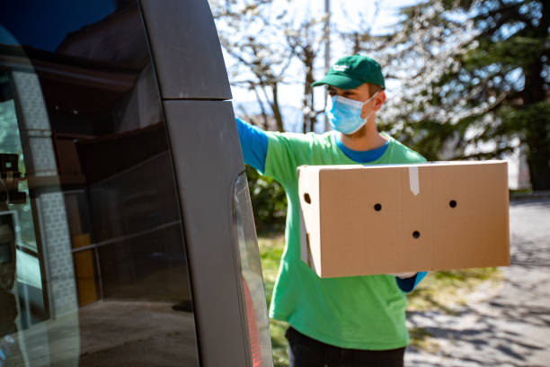 young adult home delivery man working during coronavirus pandemic - stock photo - essential workers stock pictures, royalty-free photos & images