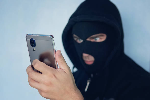 Young adult in black clothes with hidden face looks at smartphone screen. Ill-intended fraudster uses mobile. Fraudster calls. Mobile racket. Hacker hijacks by phone. Cellphone account fraud. Scam. stock photo