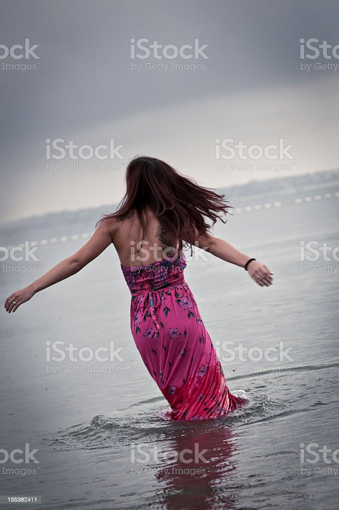 Young adult in the sea on a rainy day stock photo