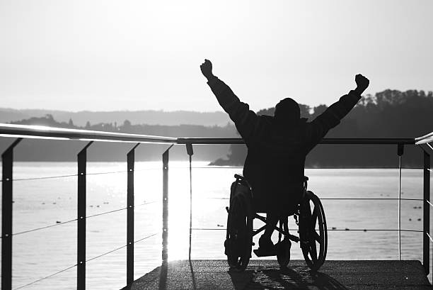 Young adult in wheelchair raising his arms outdoors. stock photo
