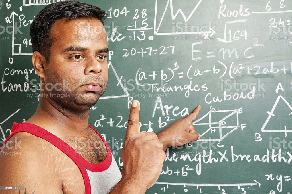 Young Adult Indian Male Teacher explaining Mathematics problems on Greenboard stock photo