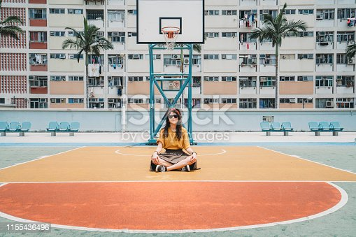 Young adult influencer on a colourful basketball playground in Hong Kong city