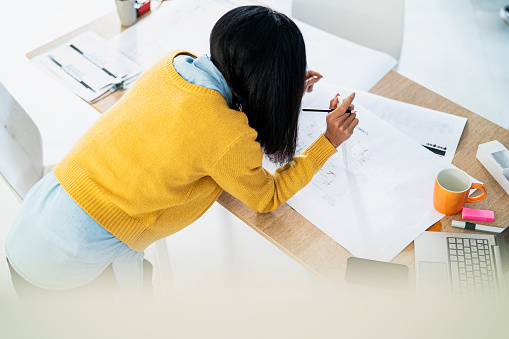 High angle shot of young adult latin architect leaning on desk while working on blueprint
