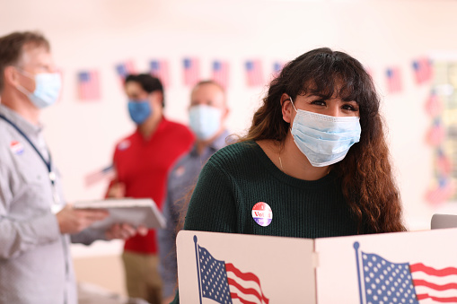 Latin descent, young adult woman votes in the USA election wearing a protective mask to protect herself against COVID-19 or other infectious diseases.