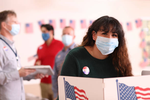 Young adult, Latin descent woman votes in USA election wearing mask. stock photo