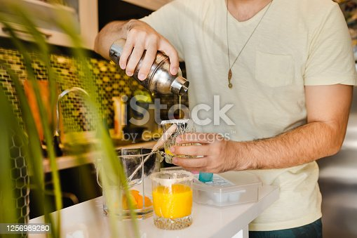 Young Adult Making Cocktails and having fun at Home