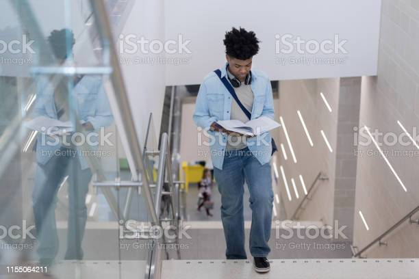 Young adult male is distracted by textbook while climbing stairs picture id1155064211?b=1&k=6&m=1155064211&s=612x612&h=ldab8izmlhfgneqlpkeaj9268iu3vnalbcakcjt3qic=