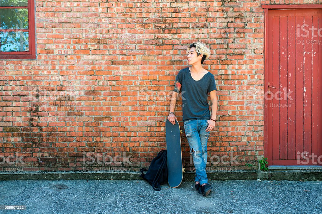 Young adult male leaning against a wall stock photo