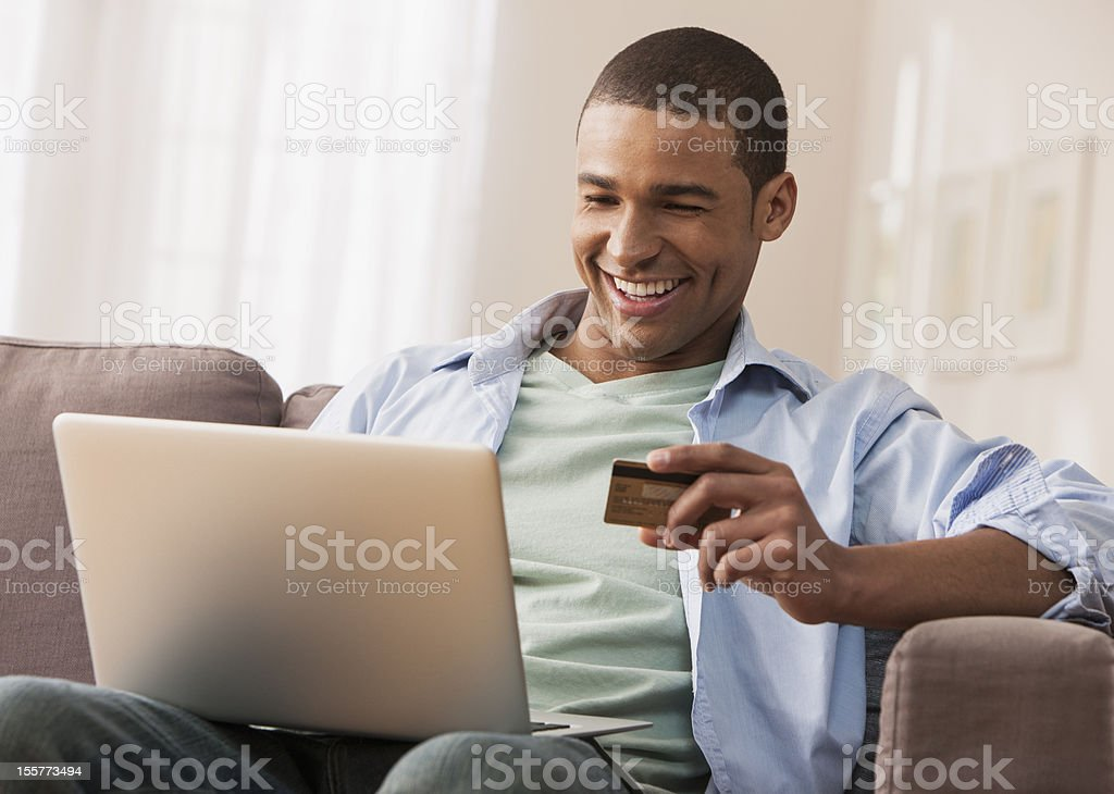 Young adult male making online purchase stock photo