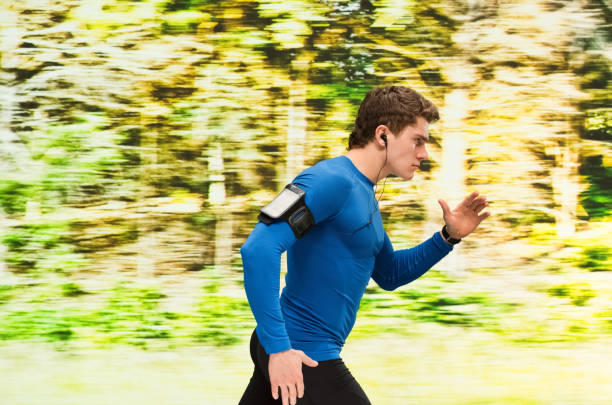 Young adult male running outside stock photo