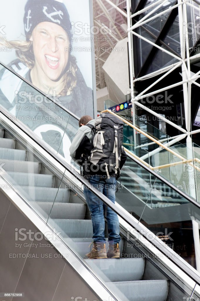 Macho adulto jovem, subindo uma escada rolante no Aeroporto Internacional de Keflavík, Islândia - foto de acervo