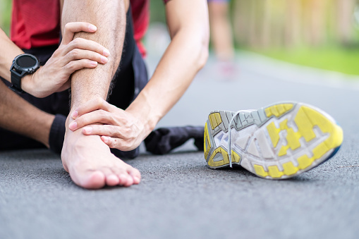 istock Young adult male with his muscle pain during running. runner man having leg ache due to Ankle Sprains or Achilles Tendonitis. Sports injuries and medical concept 1251303872
