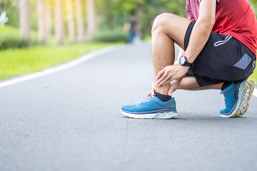 istock Young adult male with his muscle pain during running. runner man having leg ache due to Ankle Sprains or Achilles Tendonitis. Sports injuries and medical concept 1251304657