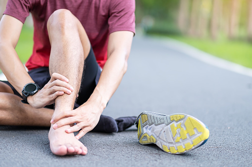 istock Young adult male with his muscle pain during running. runner man having leg ache due to Ankle Sprains or Achilles Tendonitis. Sports injuries and medical concept 1251305539