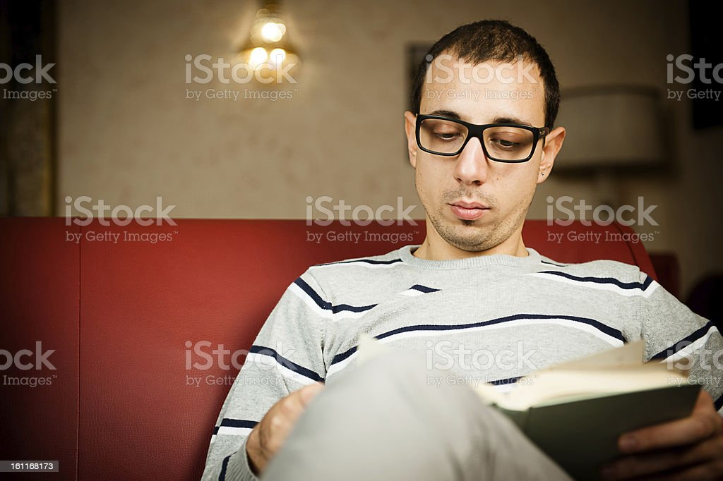Young adult man absorbed in the reading of a book royalty-free stock photo