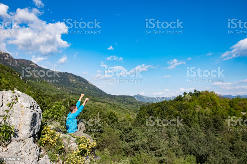 Young Adult Man Celebrating Achievement on Top of a Hill in Nature.