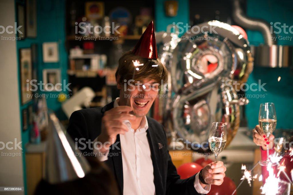 Jungen Erwachsenen Mannes feiert mit Freunden Silvester oder achtzehnten Geburtstag in gemütlichen Wohnung innen – Foto