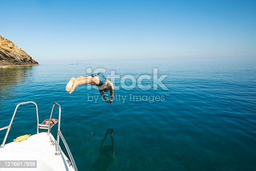 Young adult man diving from his yacht