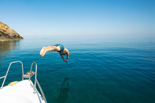 Young adult man diving from his yacht stock photo