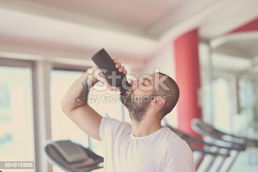 istock Young adult man drinking bottle of water on trreadmill 594915866