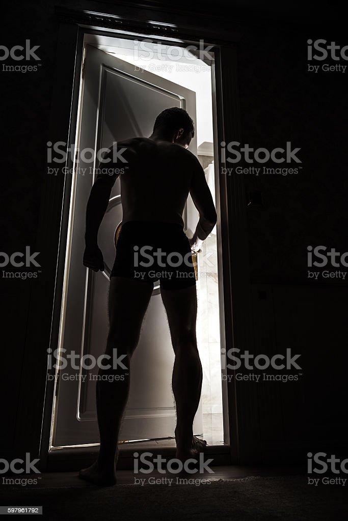 Young adult man enters opening door from dark stock photo