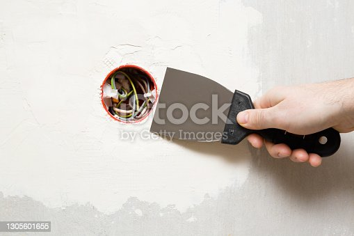 Young adult man hand using spatula and plastering wall with white fresh putty around new plastic outlet. Closeup. Repair work of home.